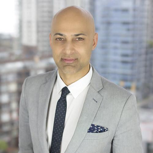 Dr. Paul Waraich wearing grey suit in front of buildings