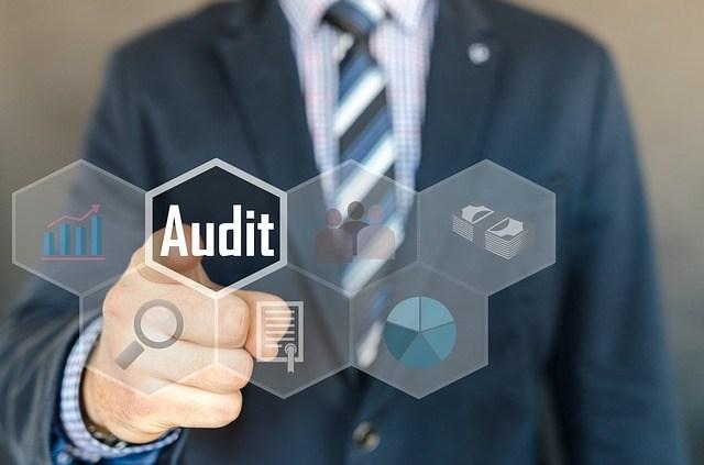 Man pushing electronic audit button