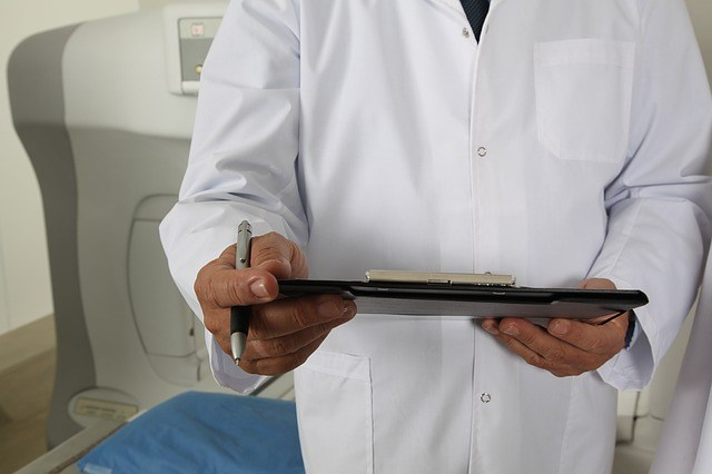 Doctor in white coat with pen and ipad