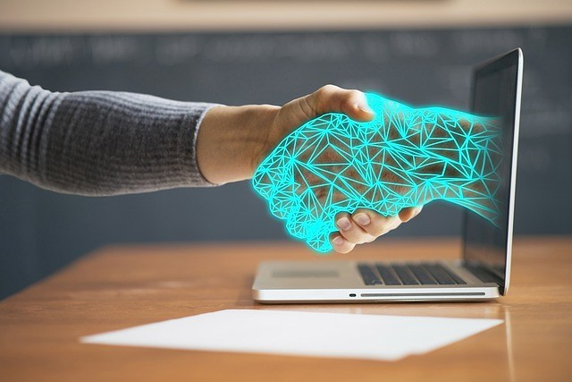 Human hand shaking electronic hand extended from computer
